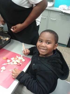A young boy prepares ingredients fin the Kidz Kook cooking class.