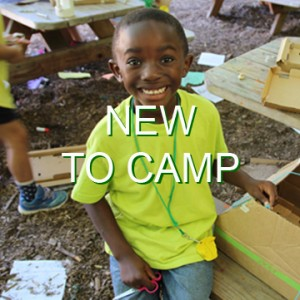 "A boy sitting on a picnic table smiles while building with cardboard. The words, ""New to camp"" are written across the photo."