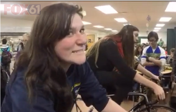 A Common Ground High School student rides a training bike in the cafeteria during lunch.