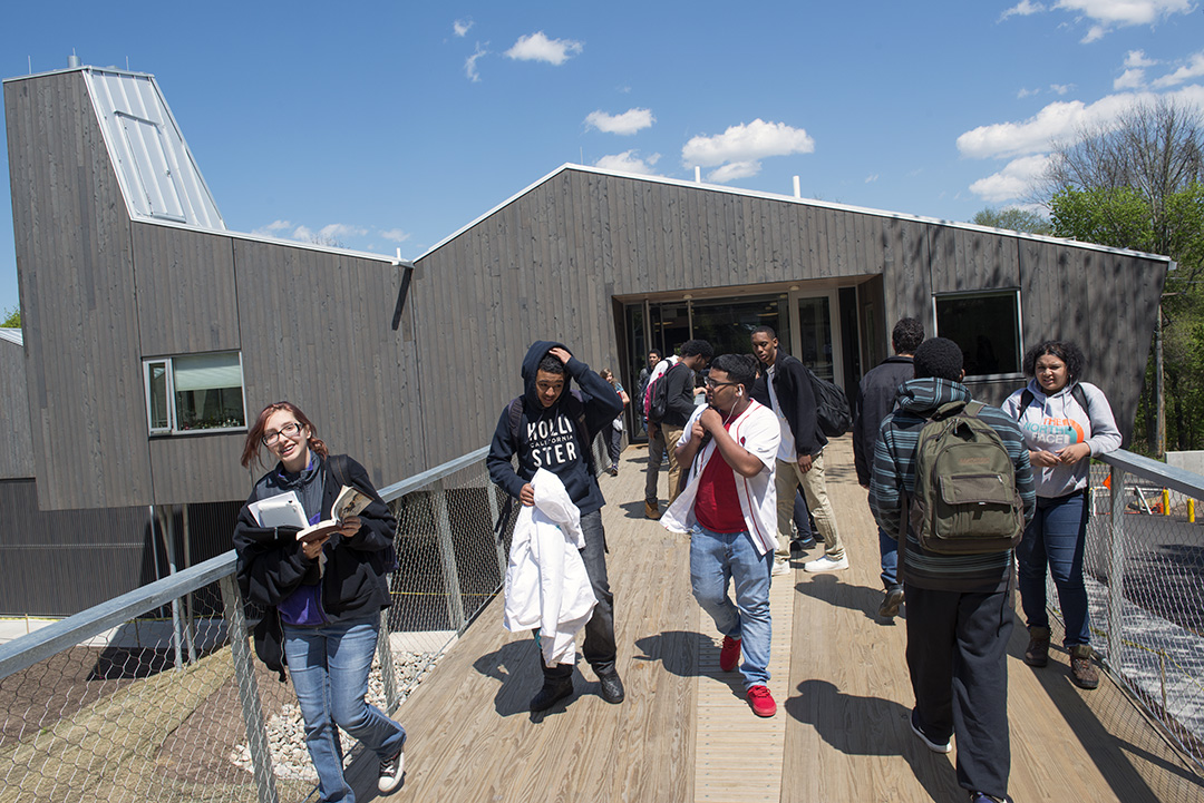 Common Ground High School students walk along the bridge by the new building.