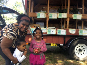 A family purchases fruit and vegetables at the CitySeed and Common Ground Mobile Market.